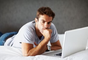 Portrait of a thoughtful young man using laptop while lying on bed at home - Indoor
